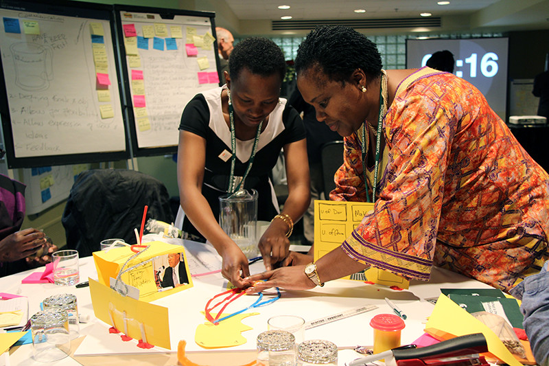 Two female African attendees working on a colorful illustration